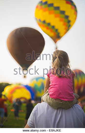 Rear view of mid adult man and daughter watching hot air balloons at festival - Stock Image