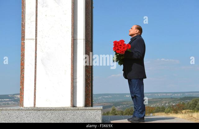 Former Italian Prime Minister Silvio Berlusconi pauses before placing flowers at a memorial to the soldiers from - Stock Image