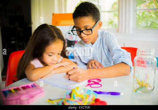 Boy and girl crayon drawing at kitchen table - Stock-Bilder