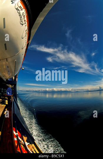 Alaska Cruise ship Inside Passage sunny weather fisheye view cruise ship water snow capped mountains life boat - Stock Image
