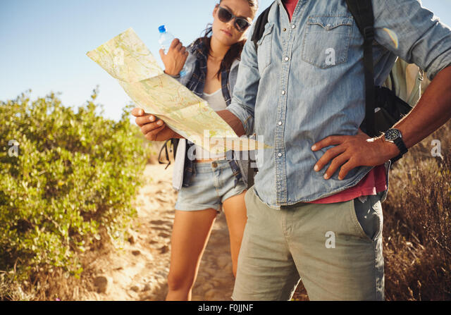 Hiker couple on country walk. Man with map and with woman standing my holding water bottle. Couple stopping to check - Stock Image