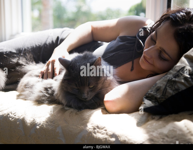 woman on a window bench with her cat - Stock Image