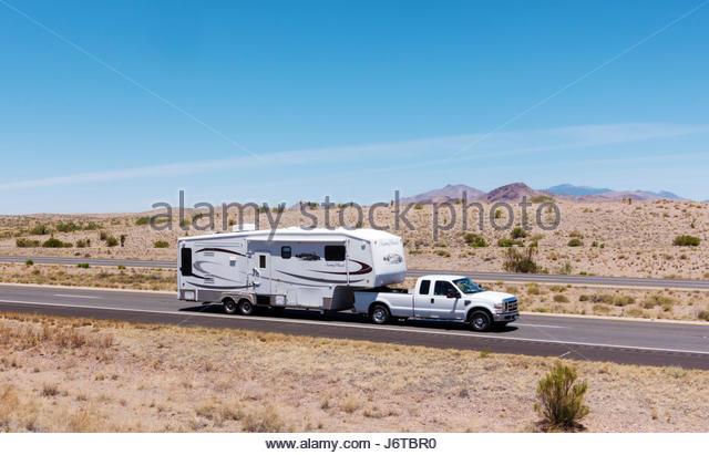 Pickup towing fifth wheel travel trailer on I-10 in southeastern Arizona - Stock-Bilder