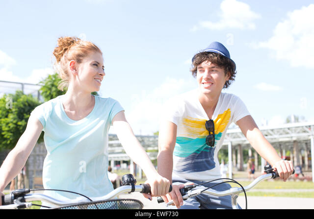Smiling couple looking at each other while cycling in city - Stock Image