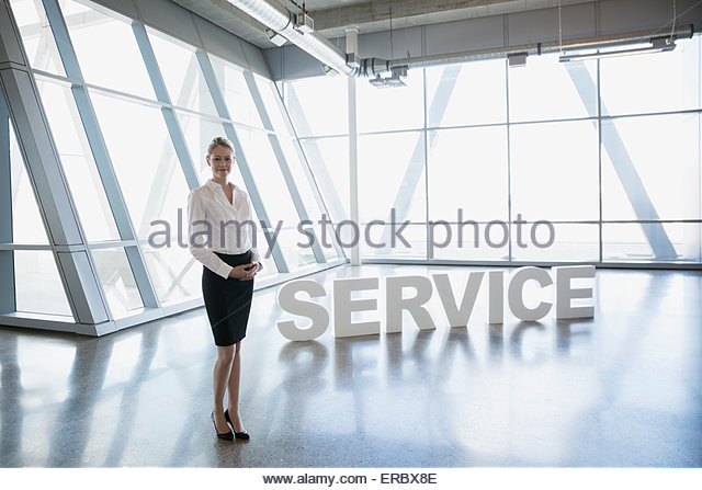 Portrait confident businesswoman near 'Service' letters - Stock Image