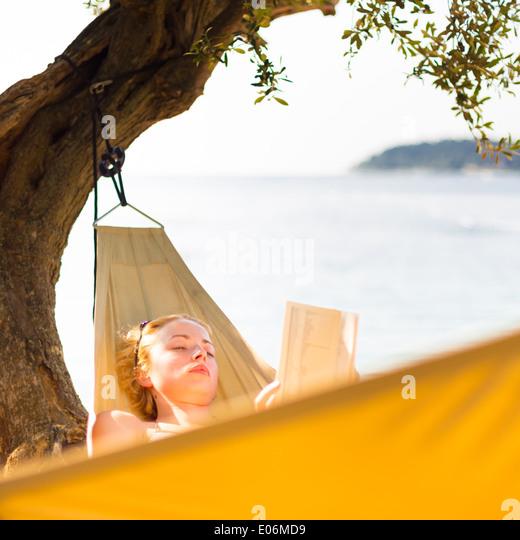 Lady reading book in hammock. - Stock Image