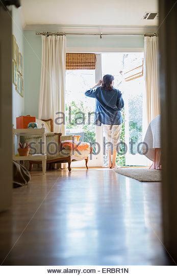 Brunette woman standing at patio doorway - Stock-Bilder