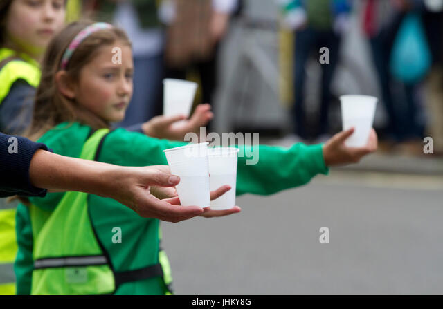 Young women handing up water to road runners - Stock Image