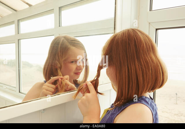 Girl plaiting hair in holiday apartment porch - Stock-Bilder