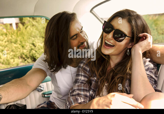 Young couple laughing in back seat of car - Stock Image