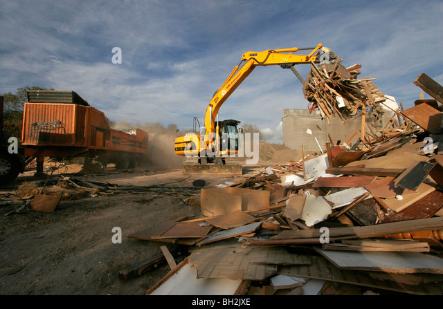 A JCB digger loading recycled wood into a chipper - Stock Image