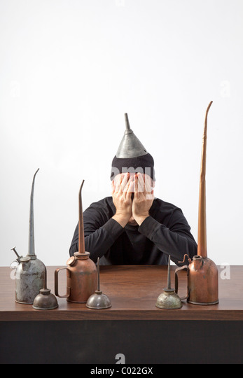Man with hands over face sits at desk with oil cans - Stock-Bilder