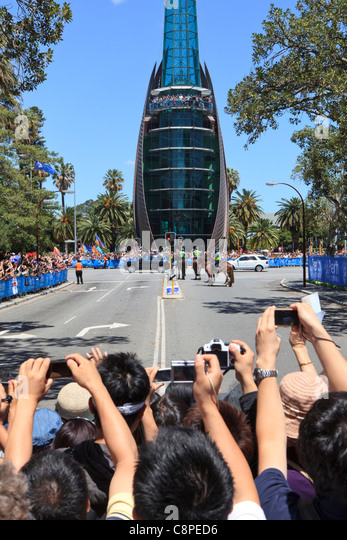 Crowds of people behind a barricade take photographs of The Queen's Range Rover as it passes the Bell Tower - Stock Image
