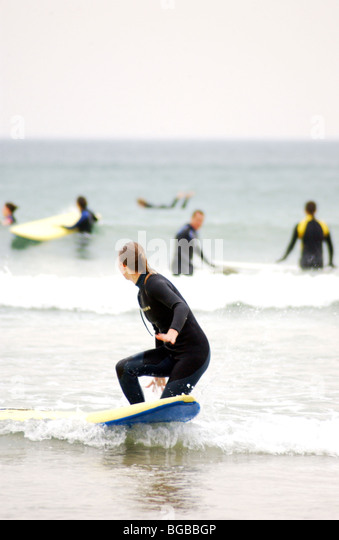 Royalty free photograph of female surfer in the sea on a cold winter day in Cornwall UK - Stock Image
