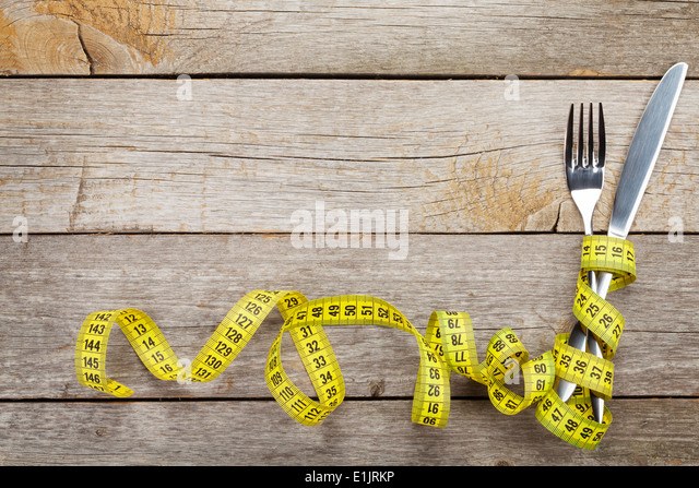 Measure tape with knife and fork. Diet food on wooden table with copy space - Stock Image