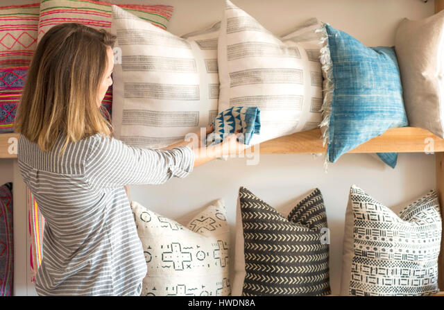 Rear view of female interior designer trying textile against cushions in retail studio - Stock-Bilder