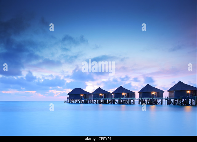 Water villa cottages at sunset on island of Kuredu, Maldives, Lhaviyani atoll - Stock-Bilder