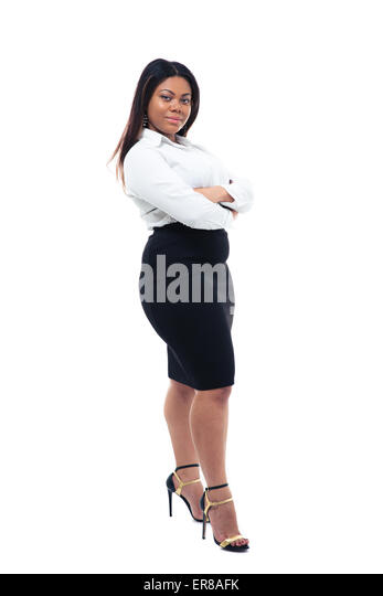Full length portrait of afro american businesswoman standing with arms folded isolated on a white background. Looking - Stock Image