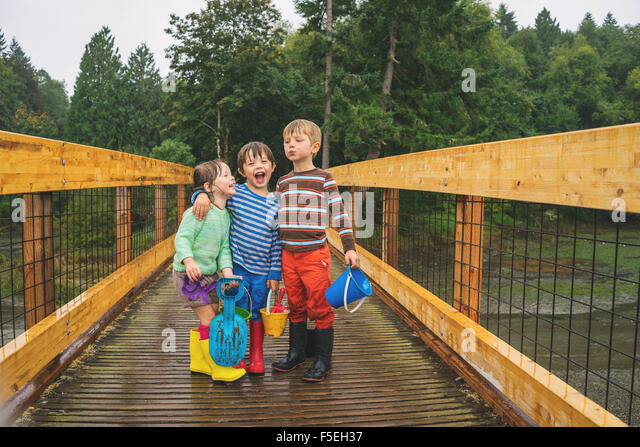 Two boys and a girl standing on a wooden bridge in the rain - Stock Image
