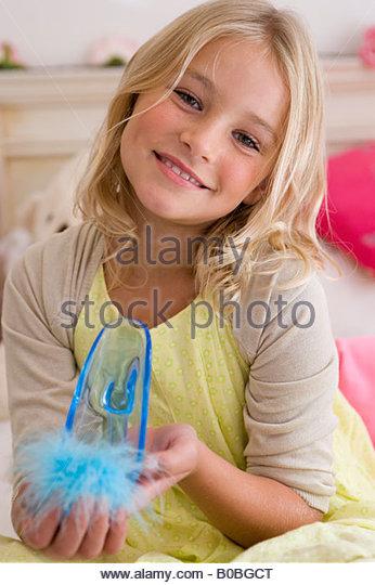 Girl  holding dress-up shoe, smiling, portrait - Stock Image