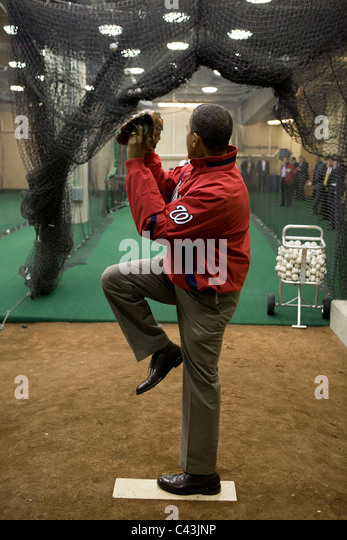 President Barack Obama warms up before throwing out the ceremonial first pitch on opening day of baseball season - Stock Image