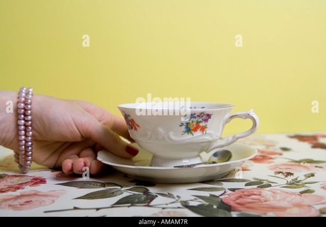 A woman's hand holding a cup and saucer - Stock Image