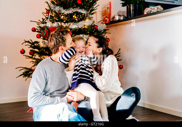 Parents kissing daughter while sitting against Christmas tree at home - Stock-Bilder
