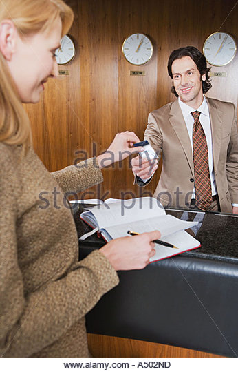 Receptionist giving pass to businessman - Stock Image