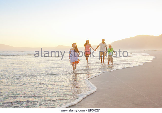 Happy family holding hands on sunny beach - Stock Image