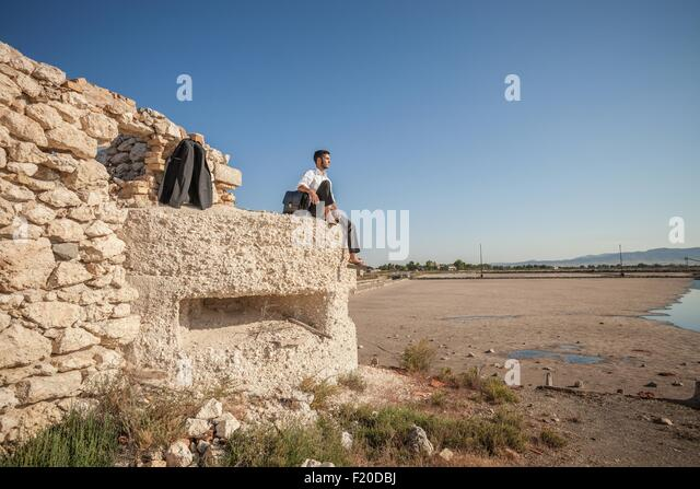 Mid adult business man looking out at sea from beach wall - Stock Image