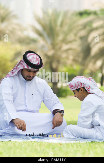 A father and son playing chess in a park - Stock-Bilder