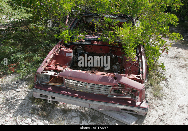 Grand Turk Cockburn Town abandoned junk auto chassis overgrown tree - Stock Image