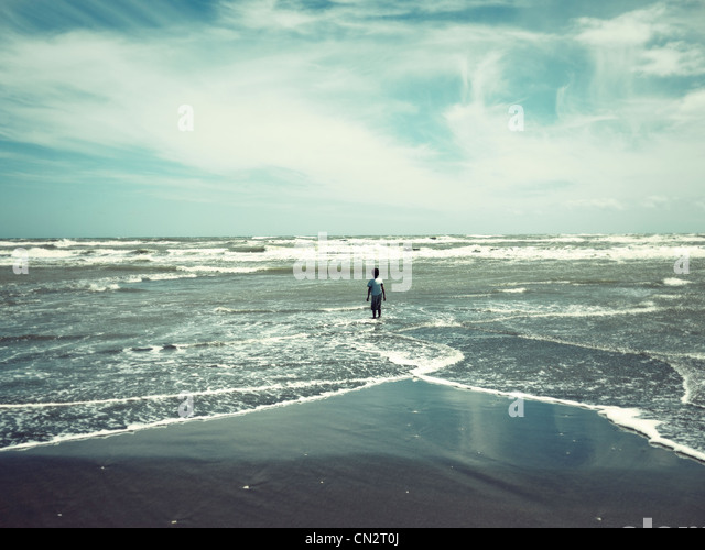 Alone: boy on beach, New Zealand. - Stock Image