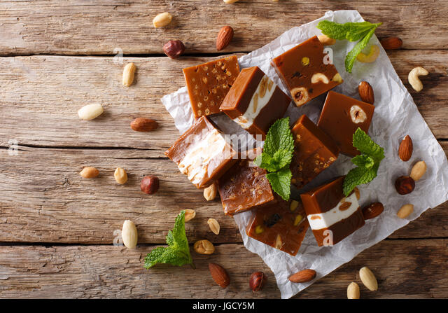 Caramel candy with nuts close-up on the table. horizontal view from above - Stock Image
