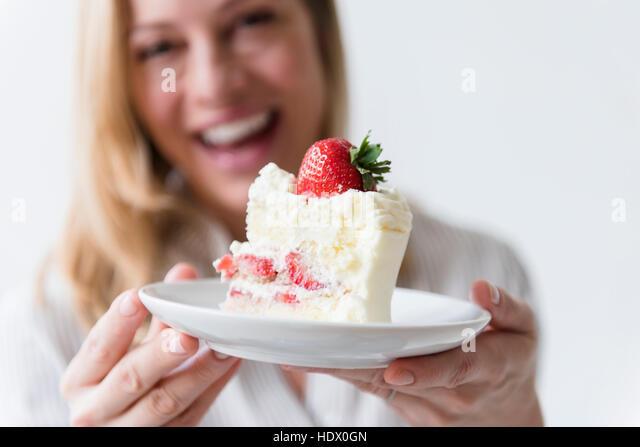Caucasian woman holding slice on vanilla cake with strawberry - Stock Image