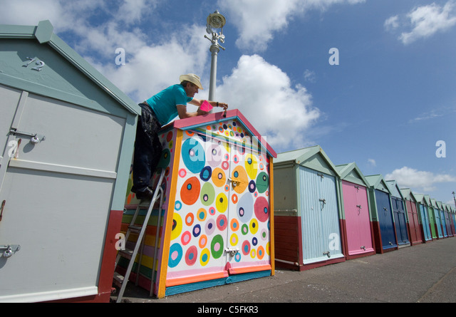 A rebel beach hut owner decides to be different and defy the rules about regulation paint colours. - Stock Image