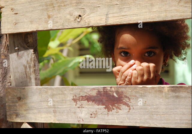 Bashful little girl hiding behind the fence in Luperon,Dominican Republic. - Stock Image