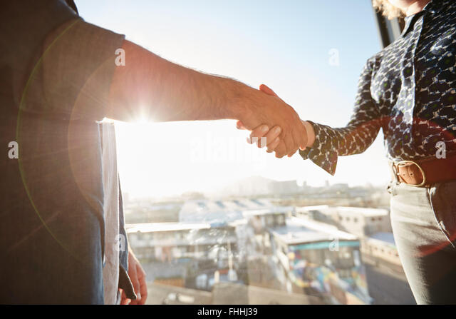 Handshake of two associates with sunlight. Male executive shaking his hand with female colleague, focus on hands. - Stock Image