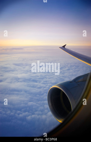Jet Engine And Wing During Flight At Sunset - Stock Image
