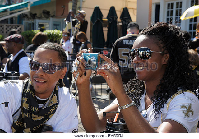 Miami Beach Florida Ocean Drive Super Bowl XLIV Week NFL football New Orleans Saints fans Black man woman - Stock Image