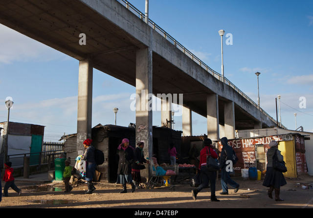 Street scene in Philippi township, Cape Town, South Africa. People are walking around the train underpass in the - Stock-Bilder
