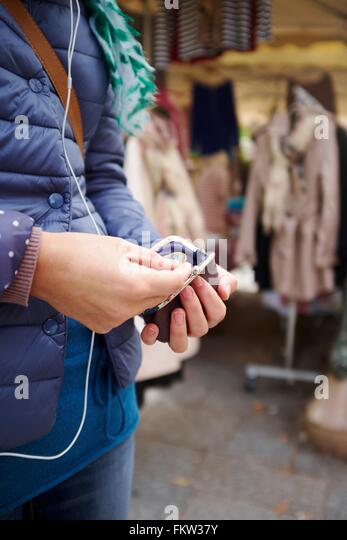 Young woman at market, taking money from purse, mid section - Stock Image