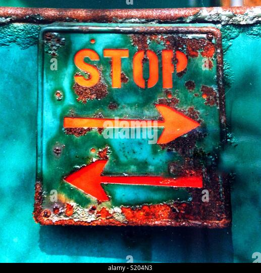 Rusted sign with writing stop and directional arrows in both directions. - Stock Image