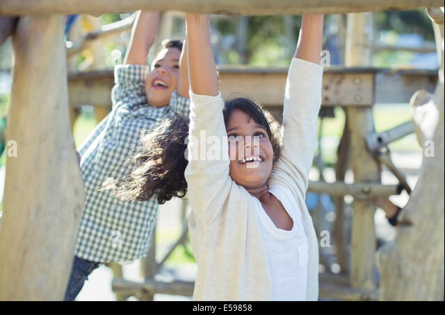 Children climbing on monkey bars - Stock Image