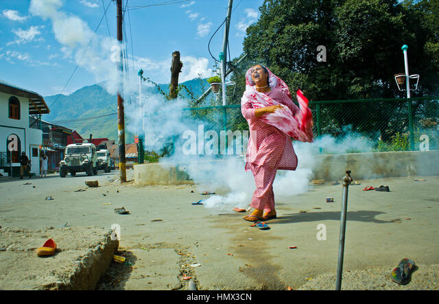 Kashmir Uprising 2016: A woman throws a tear smoke shell back at forces during a protest rally in Indian-administered - Stock Image