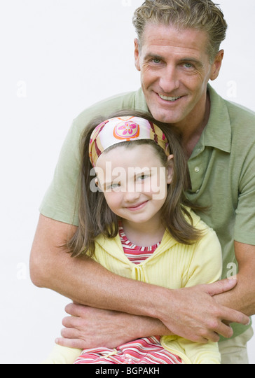 Portrait of a mature man hugging his daughter and smiling - Stock Image