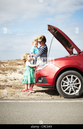 Family sitting by broken down car - Stock Image