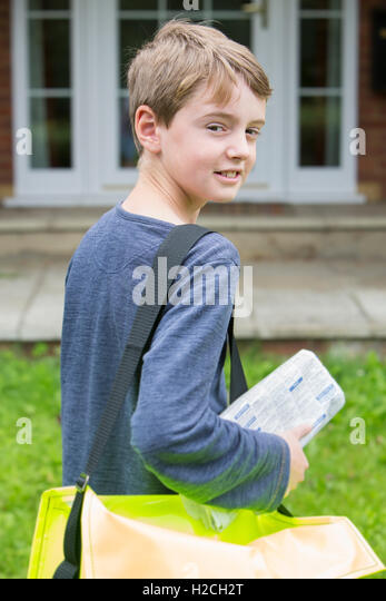 Portrait Of Teenage Boy Delivering Newspaper To House - Stock Image