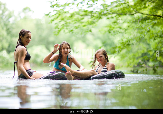Teenagers having fun in innertubes in the water - Stock Image