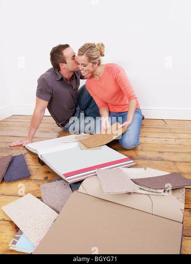 Couple looking at carpet samples - Stock-Bilder